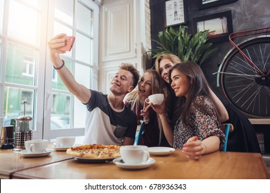 A guy taking a self-portrait with his female groupmates using his smartphone while hanging out in a coffee shop