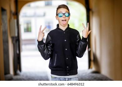 Guy teen in sunglasses walking around the city