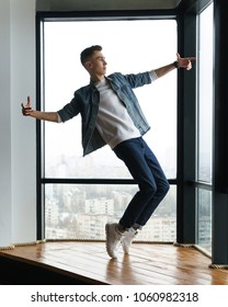 Guy teenager in stylish clothes dances at window in studio of dance. Modern dance. Hip-hop movement.