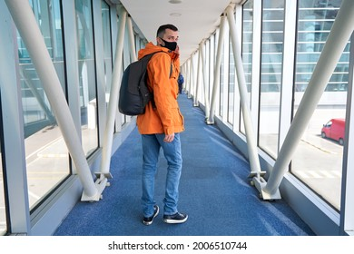Guy tourist with a backpack and in a medical mask is walking along the airbridge from the plane to the airport terminal.