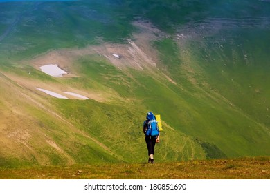 guy in tourist clothes with a backpack standing on a green hill and looks into the distance