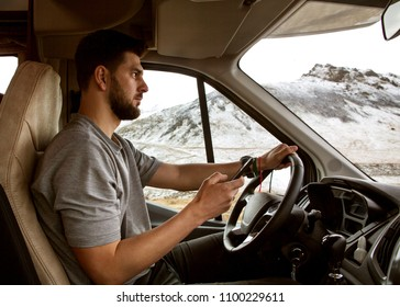 guy tourist driving a car in the mountains, traveling to Iceland.