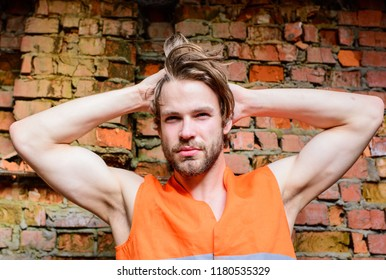 Guy tousled hair stand in front of wall made out of red bricks. Builder orange vest work construction site. Sexy macho foreman. Builder sexy muscular arms macho dream of every woman.
