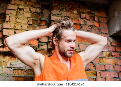 Guy tousled hair stand in front of wall made out of red bricks. Builder orange vest work construction site. Builder sexy muscular arms macho dream of every woman. Sexy macho foreman.