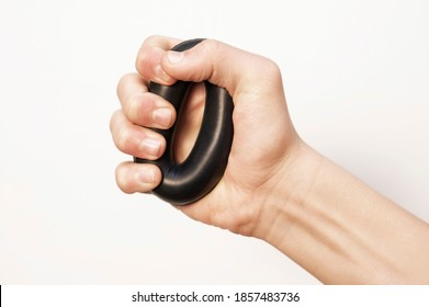Guy trains his hands squeezing a rubber expander to strengthen his arms on a light background, the concept of strength and health. Expander in a male hand on white background