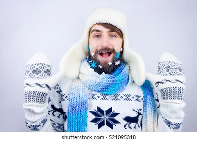 Guy with trapper hat and blue scarf wearing beard decorated with small snowflakes, putting up his hands
