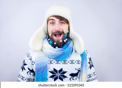 Guy with trapper hat and blue scarf wearing beard decorated with small snowflakes, being excited