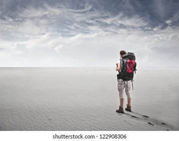 Guy with a travel backpack in a fake desert