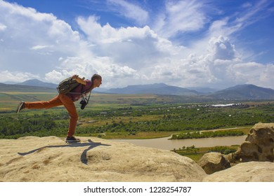 Guy with a travel backpack on the top of a boulder, photografer
