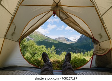 Guy in trekking boots is in a tent. View of the mountains in Norway. Camping in a hike