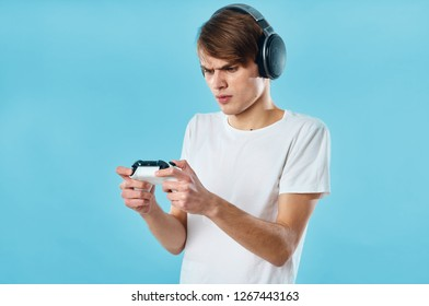 the guy in the t-shirt and headphones looks at the game joystick in bewilderment