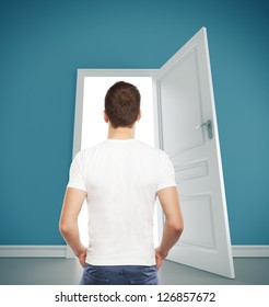 guy in T-shirt looking at  opened door