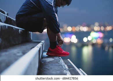 A Guy Tying Running Shoe, Preparing for Running in the Dawn, Bokeh lights background