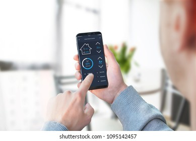 Guy use smart home control app to control lighting in living room interior.