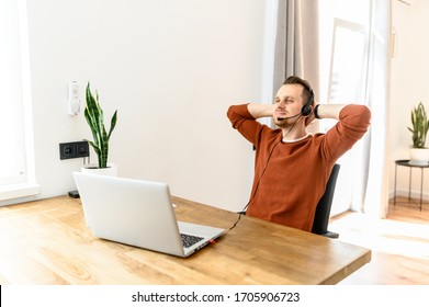 The guy uses a headset and laptop for work, he is resting in the workplace. He relaxed leaned back in his chair with his arms behind his head. Home office, freelance, work remotely