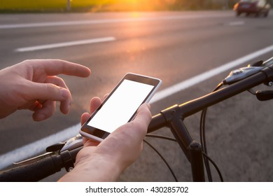 Guy is using his smartphone while he stand near by the road with bicycle - Shutterstock ID 430285702