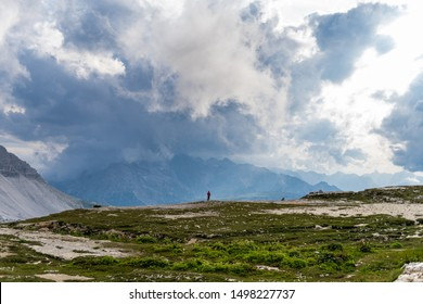 Guy walking on the edge of a mountain in Dolomites, Trentino.