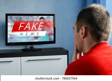 The guy watching the fake news on TV. Corrupt journalism. The false reporting. Deception, propaganda and misinformation from television. brainwashed brains of men watching TV.