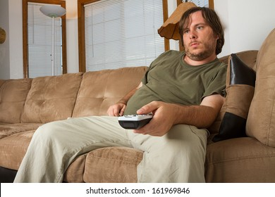 GUy watching TV with a big belly