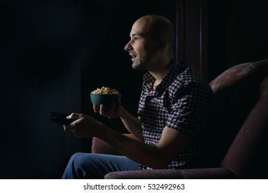 guy watching TV with remote control at home at night