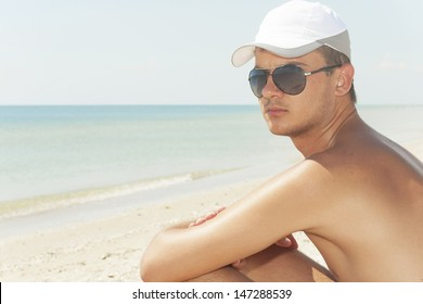 guy in wearing black glasses on a beach