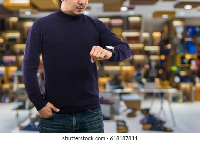 A guy wearing blank mock neck long t-shirt while standing and seeing the clock over the Abstract blurred photo of the bag and shoes store in a shopping mall, fashion mockup and designer concept