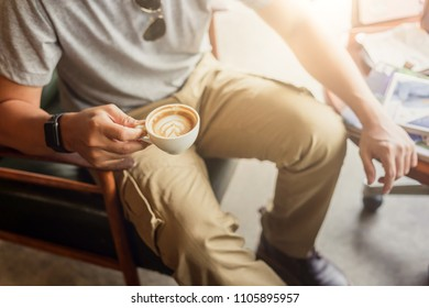 Guy wearing cargo pants and drinking a coffee in coffee shop
