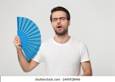 Guy wearing gasses white t-shirt feels overheated holds blue waver fan induces airflow cooling himself reducing heat pose isolated on gray studio background, summer weather, no air conditioner concept