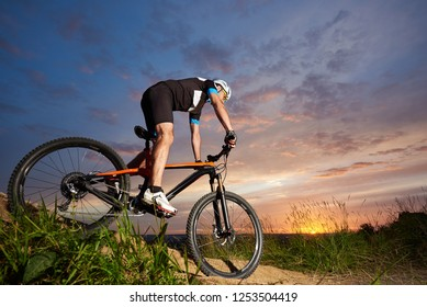 Guy wearing a helmet and sportswear on a mountain bike riding downhill under the evening sky against the sun at sunset. The concept of an active lifestyle