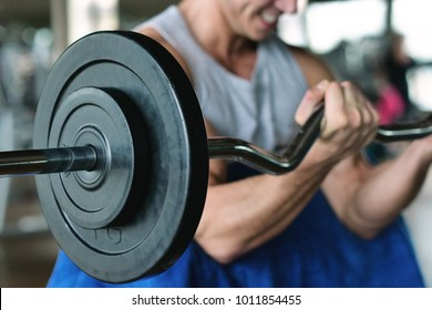 A guy, wearing a tank top in a gym, trains his body to stay fit and have defined muscles. The athlete raises heavy weights and fatigue. Concept of: sport, gym, muscles and fitness