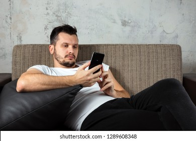 The guy in the white shirt is lying on the couch and sitting in the phone. The concept of laziness, apathy, frustration, procrastination, the person at home. copy space.