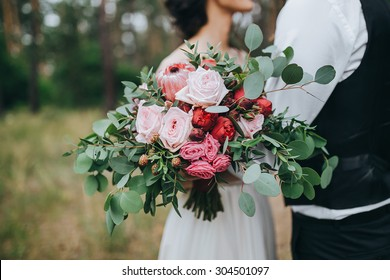 guy in a white shirt and waistcoat and a girl in a white wedding dress with a bouquet of red flowers and greens in hands stand in a clearing in the woods