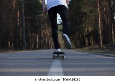 a guy in a white T-shirt skateboarding on a park road among the trees skate skateboard