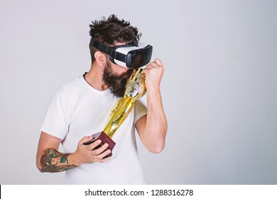 Guy won virtual competition and carries on shoulder goblet. Hipster on grateful face kisses goblet. Champion concept. Man with beard in virtual reality glasses is winner, grey background.