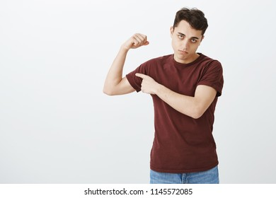 Guy working out but still weak. Portrait of gloomy displeased handsome guy in red t-shirt lifting arm and showing biceps, being displeased with muscles, staring unhappy at camera over gray wall