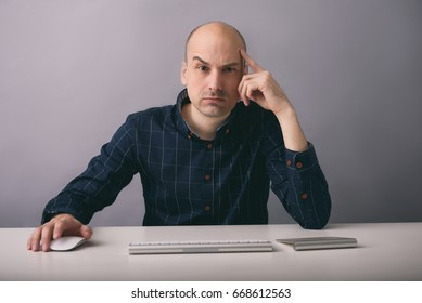 Guy works on computer. Serious man sitting at the desk and thinking