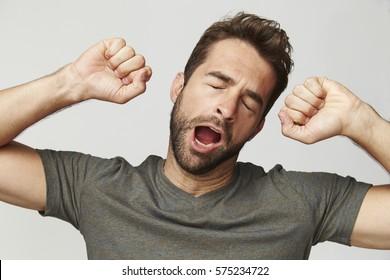 Guy yawning and stretching, studio