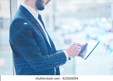 The guy's a businessman in a suit holding a tablet in hands
