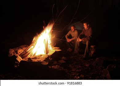 Guys camping with campfire