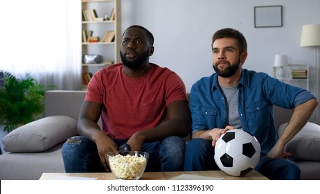 Guys frustrated by defeat of favourite team, watching football match on tv