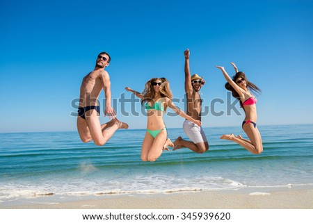 6f6c1037e5509 Guys and girls at the resort. Weekend at sea. Cheerful young people jumping  on