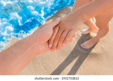 The guy's hand holds the girl's hand close-up standing next to the background of wet sand on the beach and blue sea water. A sign of love and relationships.
