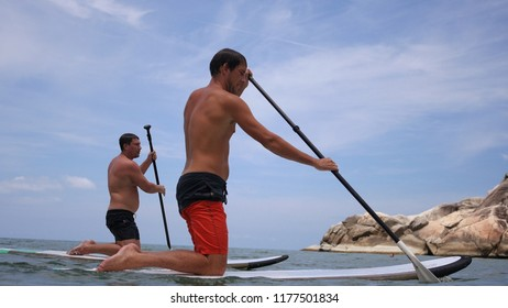 Guys learn to ride a paddle board, row with a paddle.