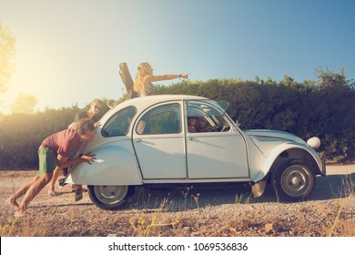 Guys pushing a broken old car with girls at the wheel during vacations.