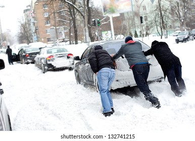 The guys are pushing a car stuck in the snow