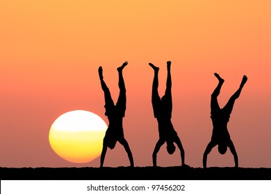 Guys silhouettes doing an acrobatic handstand on the sunset background