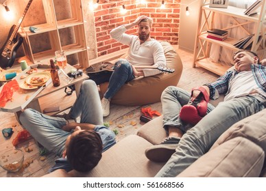Guys are sleeping in messy room after having a party at home