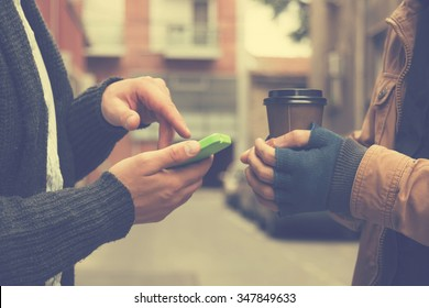 Guys using cellphone outdoors.