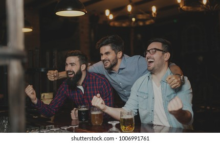 Guys are watching game and drinking beer at pub.