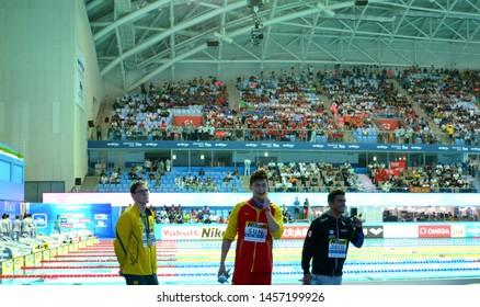 Gwangju, South Korea - Jul 21, 2019. China's Sun Yang, centre, with his gold medal as silver medallist Australia's Mack Horton, left, stands away on FINA Swimming World Championship, 400m freestyle.